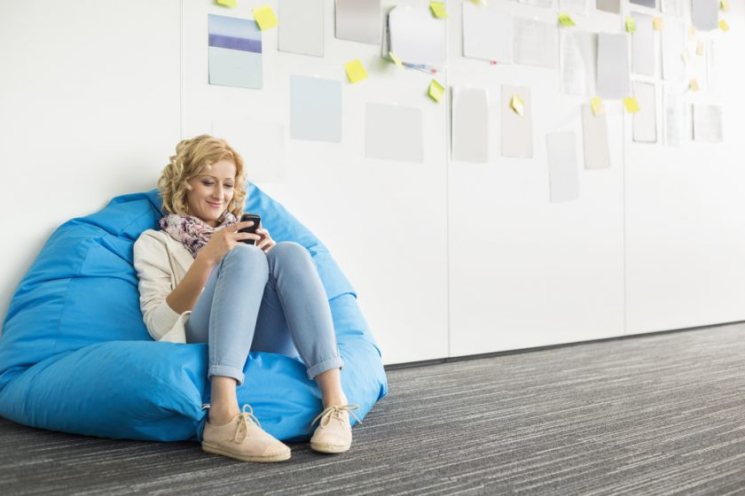 Smiling businesswoman using mobile phone on beanbag chair in creative office