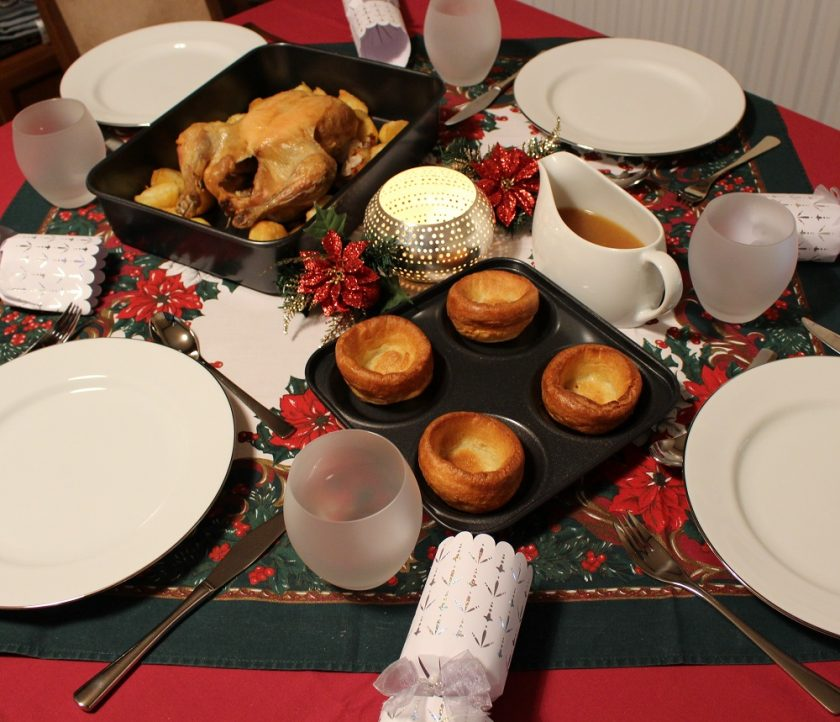 Debenhams at Christmas - Christmas dinner table featuring yorkshire puddings, chicken, gravy, Photo also shows plates, crackers and glasses, taken from left hand side near yorkshire puddings.