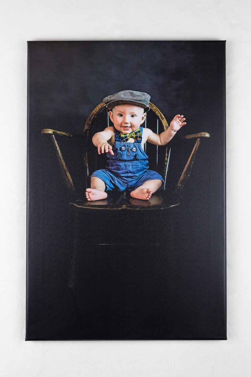 Logan sat on chair wearing dungarees and a cap sat on an old Victorian chair.