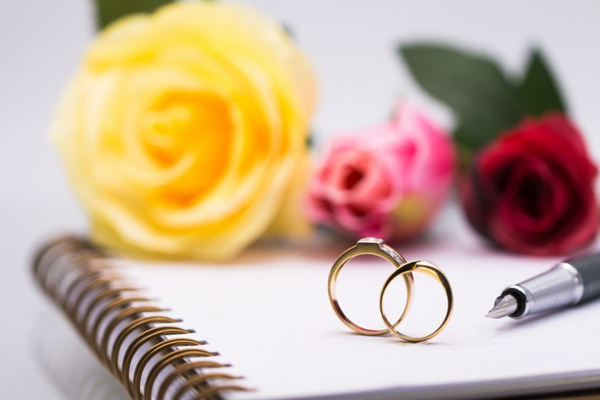 Wedding Rings sat on a paper pad with a yellow rose and other flowers in the background